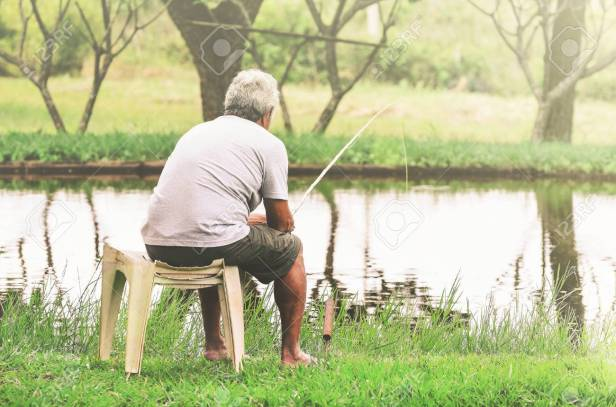 Retired old man seated next to the lake fishing and relaxing